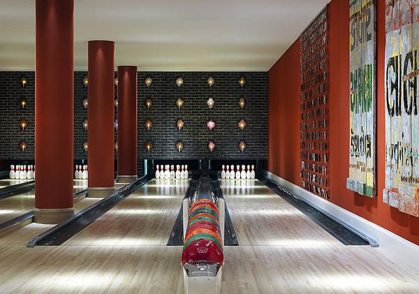 The interior design is fun and eclectic, with bold patterns and prints. It features a 1950s style bowling alley
