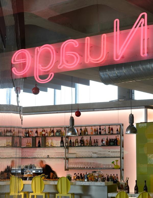 The café bar area features a neon pink sign and a range of lime green furniture and tiling. Starck aimed to create a light, airy feel across the health club, while adding a sense of fun