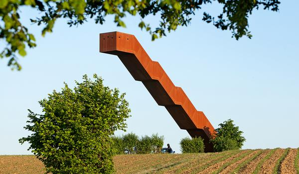 The structure appears to defy gravity. Its red-brown colour is a reference to the  ironstone found locally