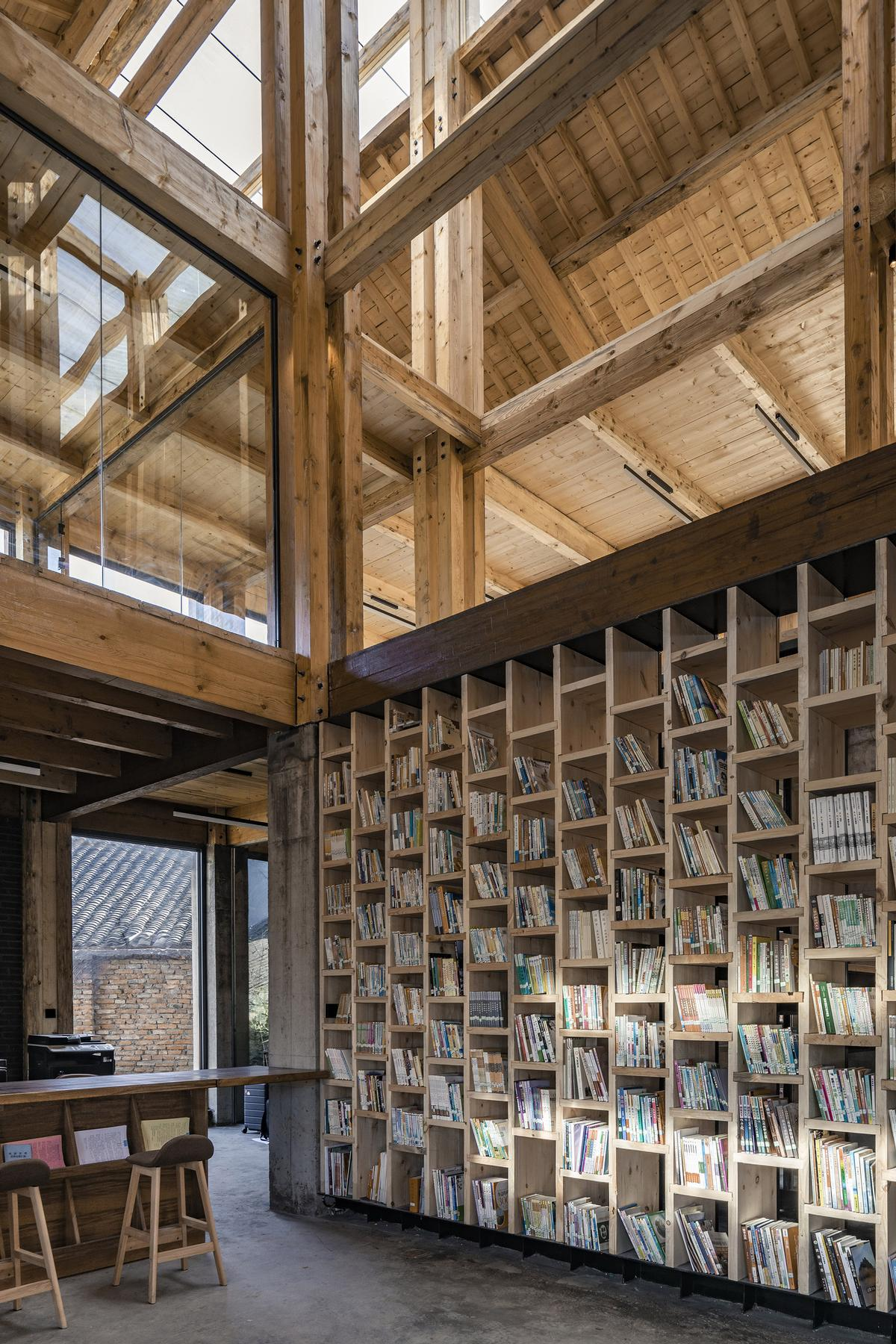 A library area is filled with books and provides spaces to sit / Jin Weiqi