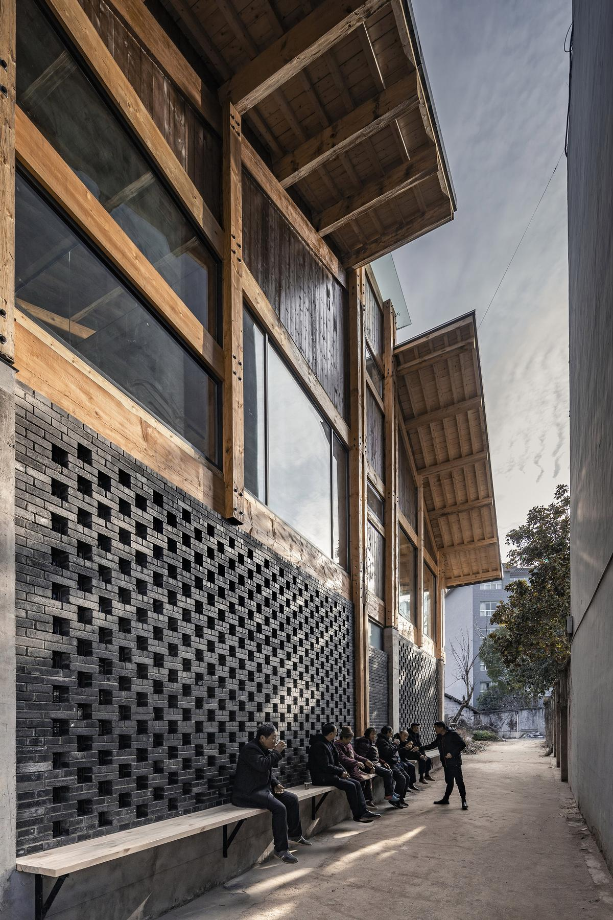 A bench along the ground-floor exterior provides a place for locals to sit and get together / Jin Weiqi