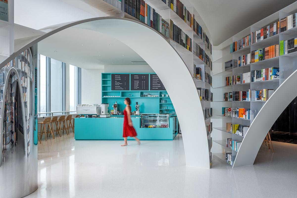 A turquoise coffee shop counter is one element that breaks up the white colour scheme / CreatAR Images