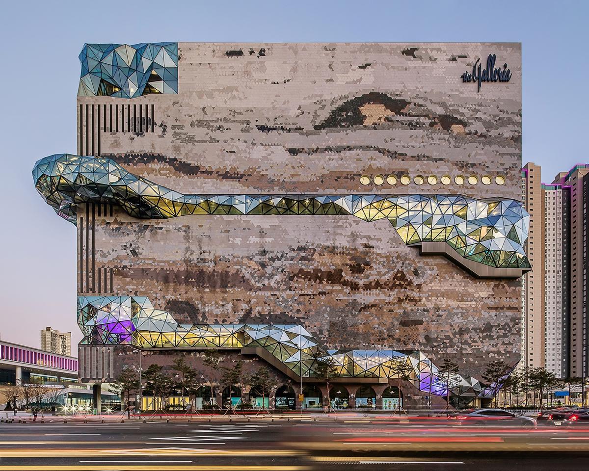 A multifaceted glass façade runs through the volume like a gemstone seam