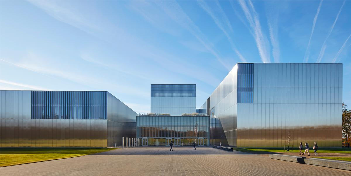 The museum rises to 100 feet at its peak, and its facade is composed of a regular grid of laser-cut, stainless steel panels / SOM