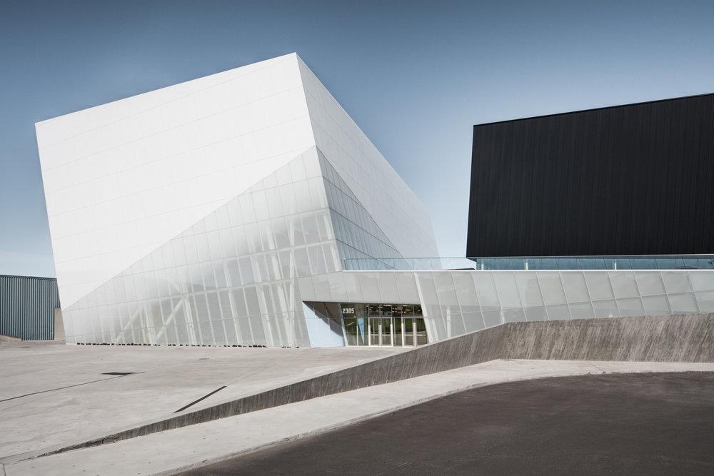 The centre is formed of two 'floating' angular volumes, one white and prism-like, the other darker and stretched horizontally