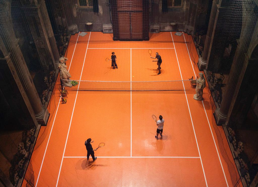 The space is set up like a typical court – complete with lines, netting, racquets, chairs, a jug of iced jasmine tea and even coaches to practice with