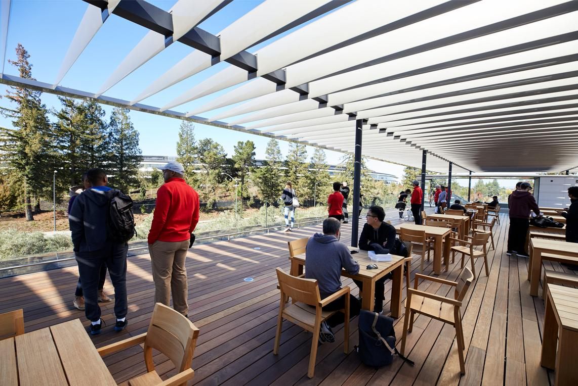 A cafe with outdoor seating lets visitors relax amidst the verdant scenery of the park / Apple