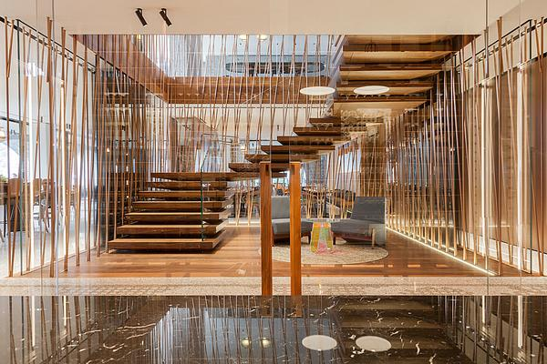 The hotel's central staircase features stacked steps that appear to float. It is made from walnut and bronze