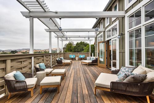 The private outdoor relaxation deck mirrors the entrance with a wisteria covered trellis, central water element, and contemporary chaise lounges