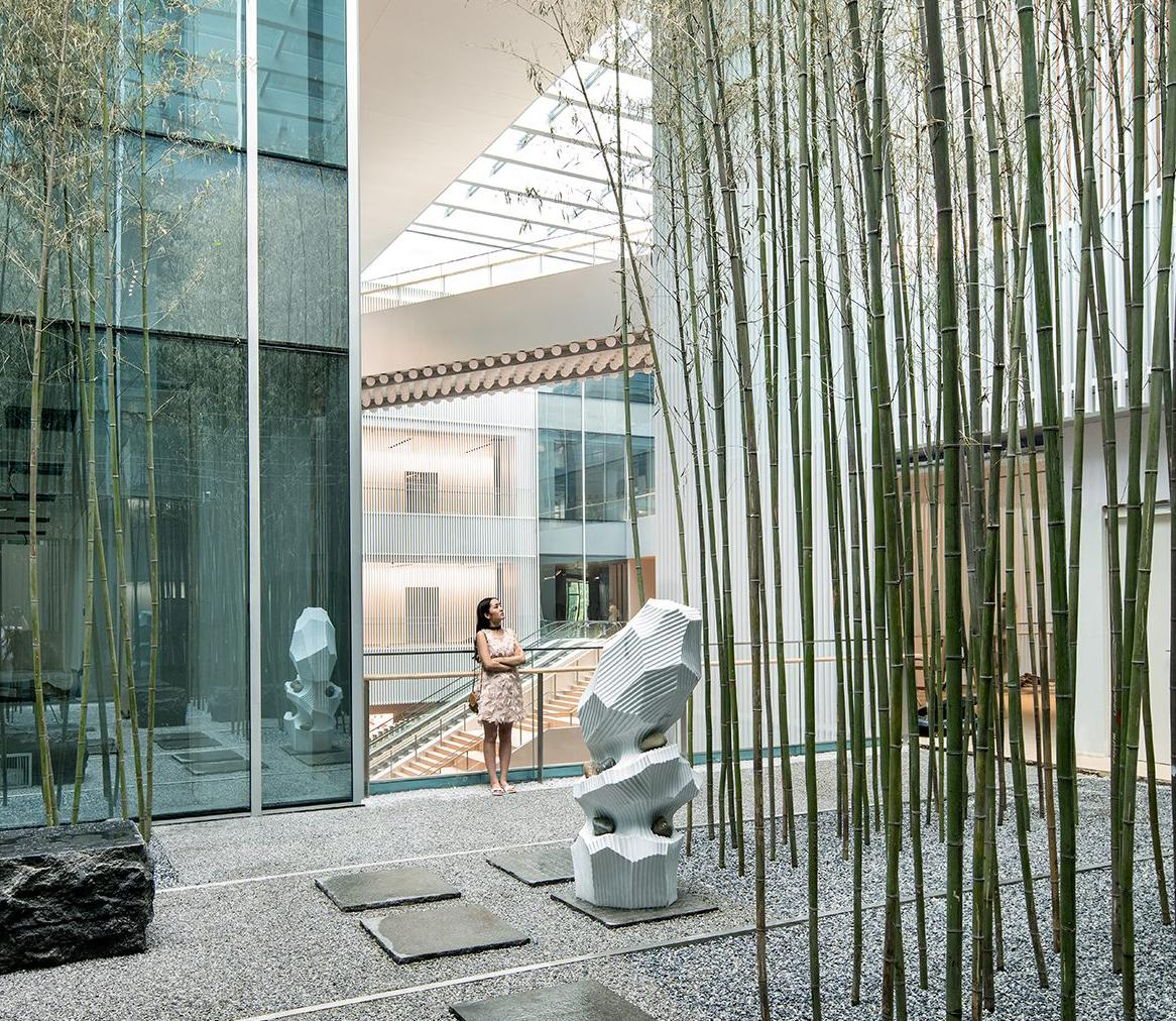 The meditation garden sits on the western side of the building's second floor. Dotted with vertical, bamboo-like installations, it is naturally lit by a skylight. / Yuzhu Zheng