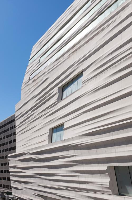 The building's innovative facade catches the changing light and shifts in appearance throughout the day.