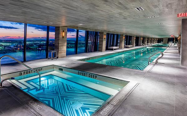 The glass skybridge that links the towers houses an indoor pool and hot tub, as well as  a residents' bar and lounge
