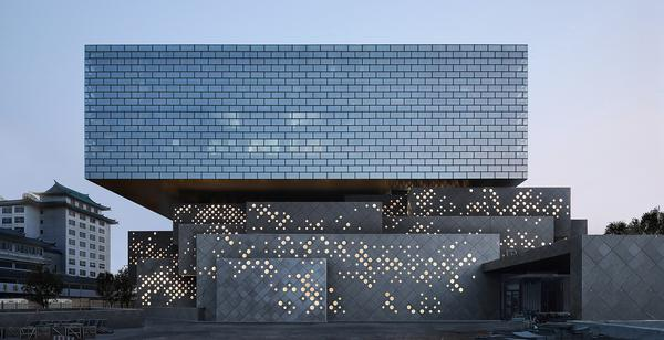 The building's nested stone volumes echo the materiality of the adjacent hutong courtyard houses