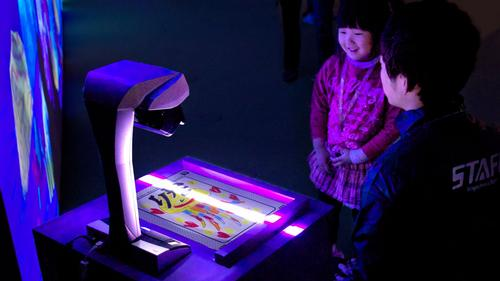 Children draw their own sea creatures in the Sketch Aquarium before scanning them and watching them come to life before their eyes / teamLab