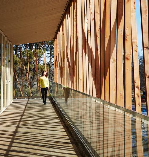 A second-flood glass walkway extends outdoors, opening up the site to the community / Steve Hall for Hedrich Blessing