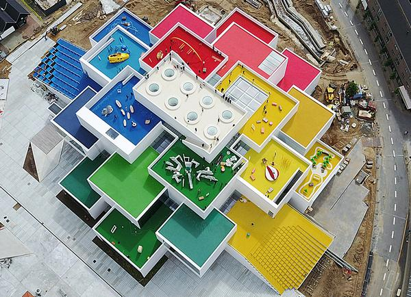 The Lego building is designed to look like a stack of Lego bricks, with a 2x4 brick on top