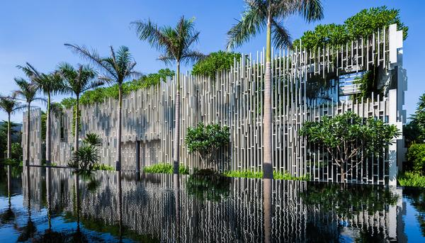 Hanging plants create the impression of walls, while the white sculptural fins filter the sunlight