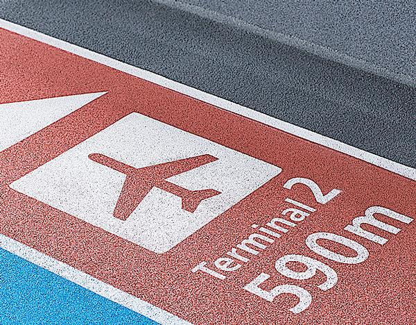 The running tracks in the airport are colour coded: red for arrivals and blue for departures. White stenciled symbols direct passengers to the correct part of the building