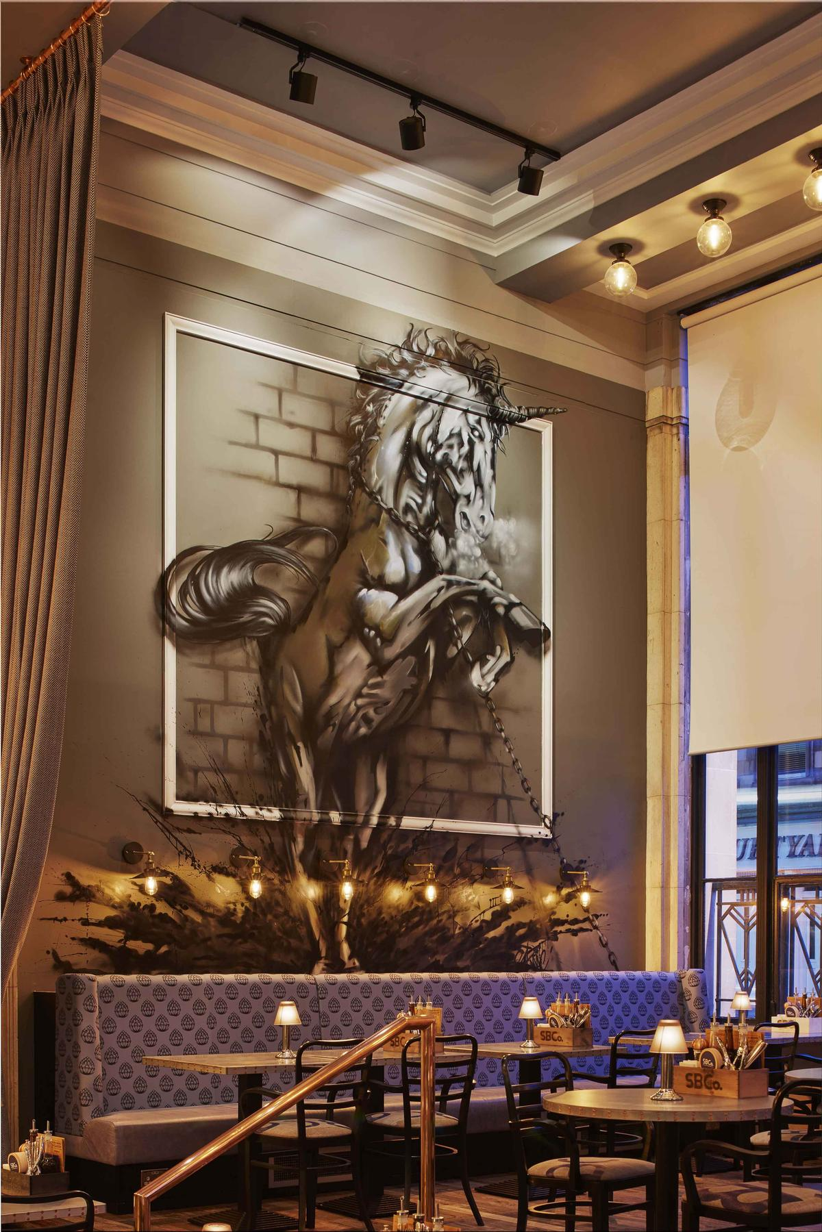 Local artist Gaz Mackay has created a large mural of a unicorn for the bar / James Harris
