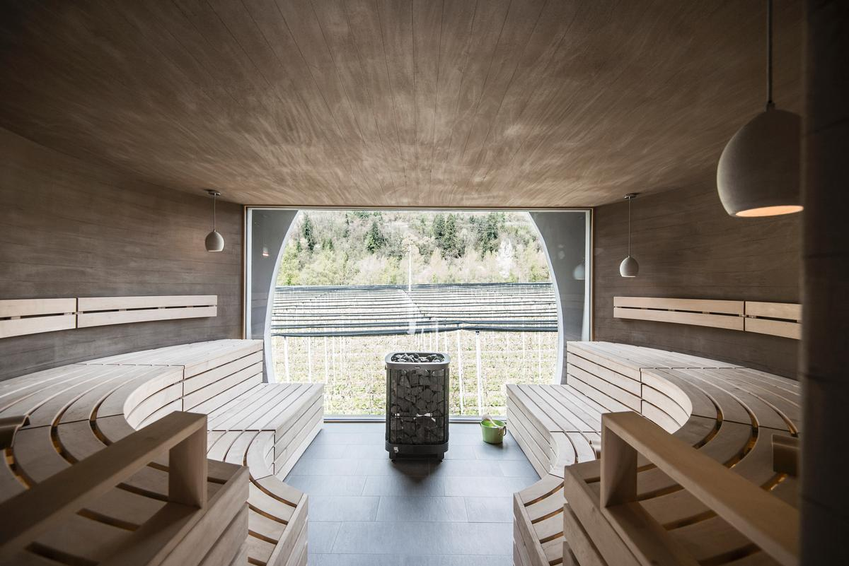 The earth-coloured concrete walls pursue the lines of the wooden slats of the sauna benches / NoA*