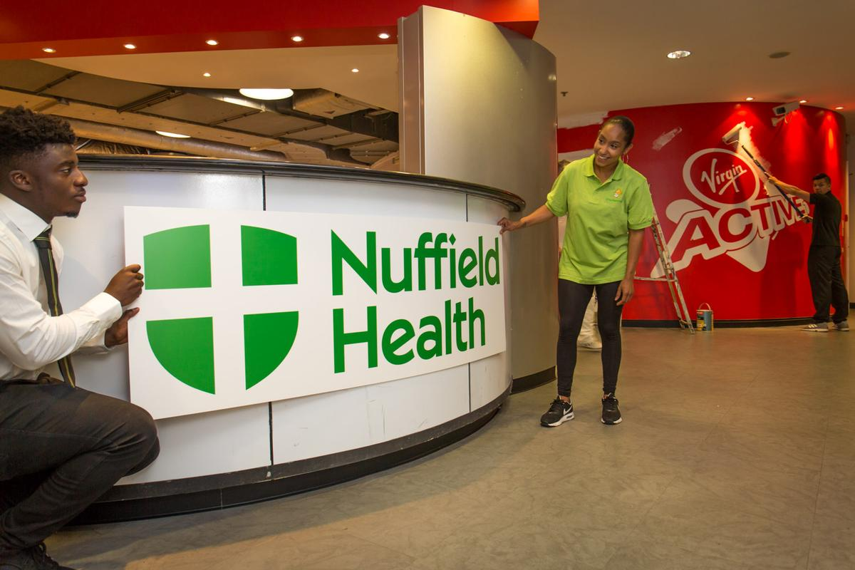 Nuffield's green shield logo being installed at a Virgin Active club, signifying the beginning of the rebranding process