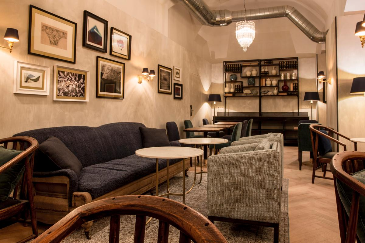 The underground breakfast room features velvet sofas, parquet floors, vintage 1970s lighting, antique doors and an industrial exposed ceiling / Midmost Hotel