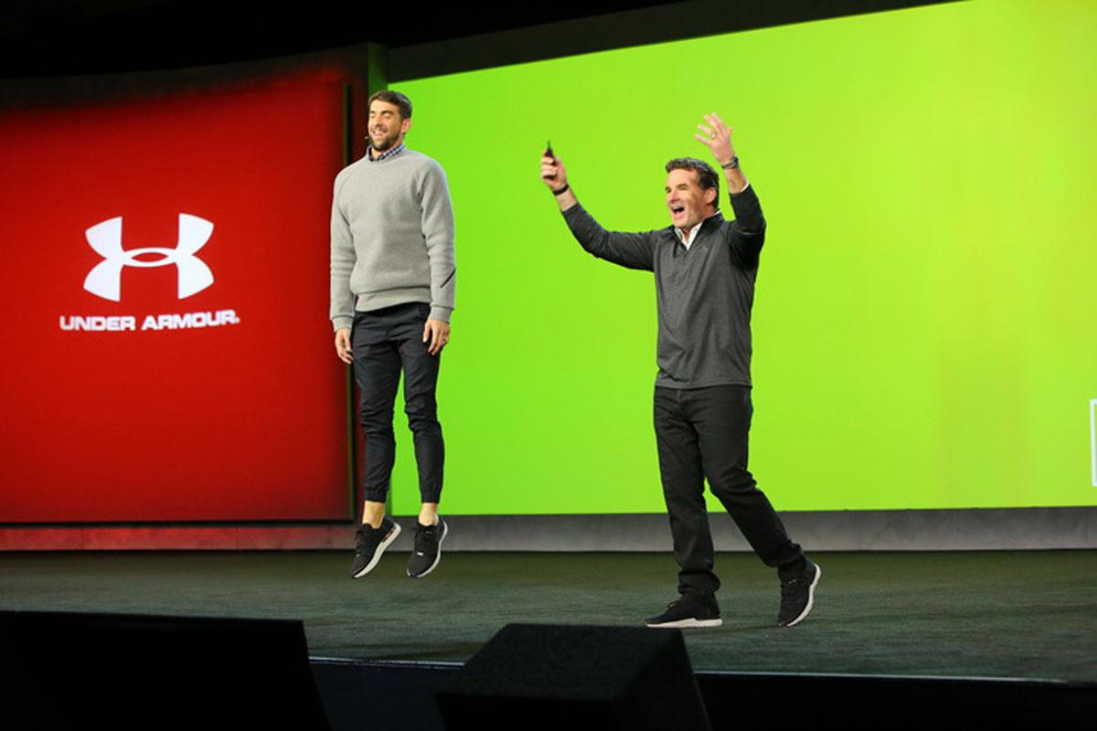 Kevin Plank on stage with Michael Phelps, who is demonstrating Record Equipped shoes, which give performance feedback.