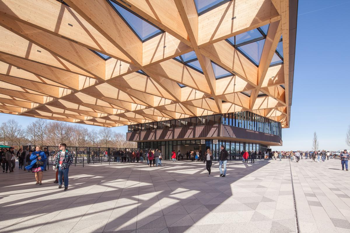 The timber roof structure, which leans on two volumes, has been created using interwoven isosceles triangles that form skylights / Mecanoo architecten