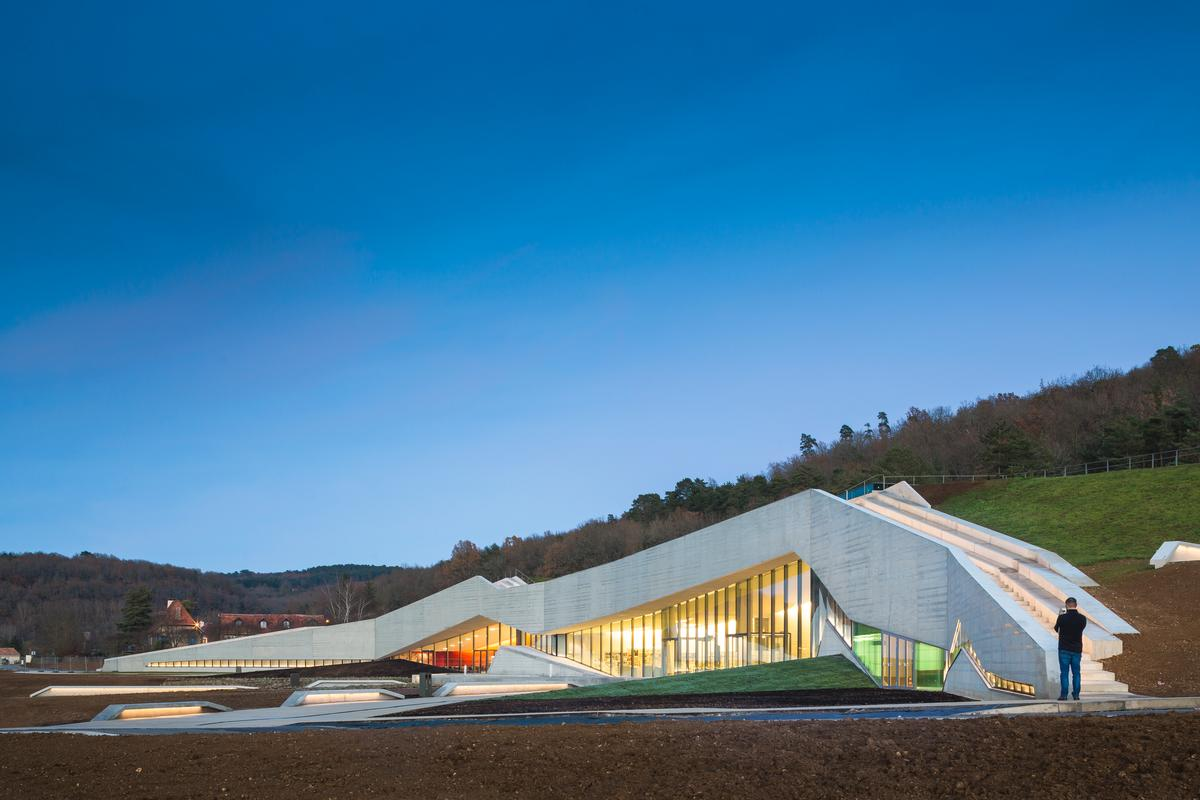 The form of the centre merges with Lascaux hill and the forest beyond / Boegly + Grazia