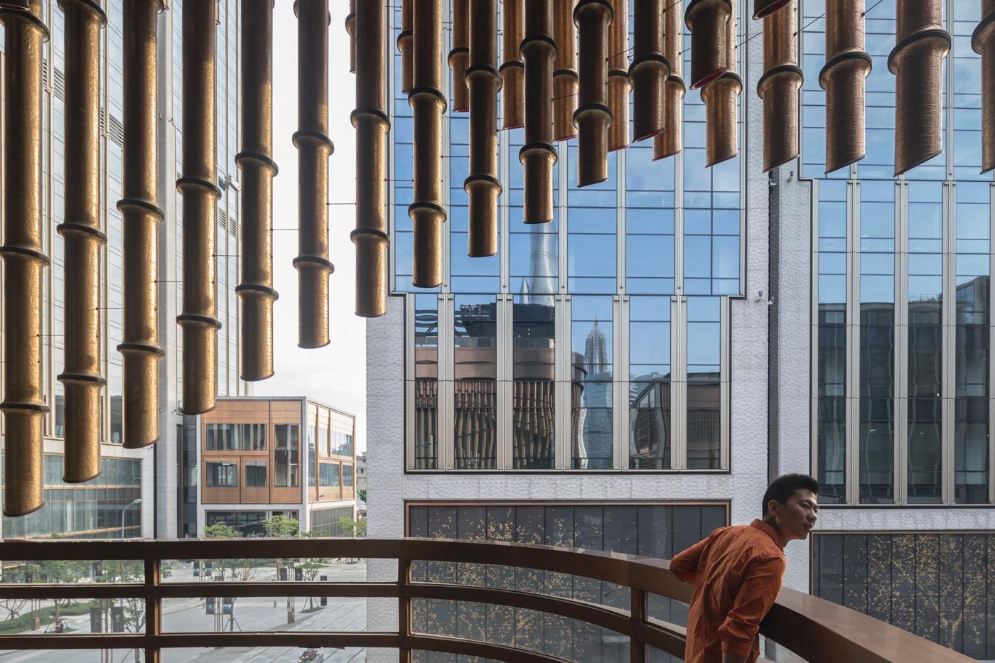 Overlapping layers of bronze tubes form the building's moving curtain / Laurian Ghinitoiu