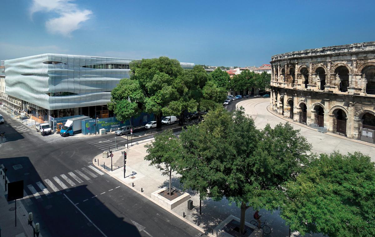 The museum has a transparent ground floor – from which visitors can view the Arena – topped by a shimmering glass façade / Serge Urvoy