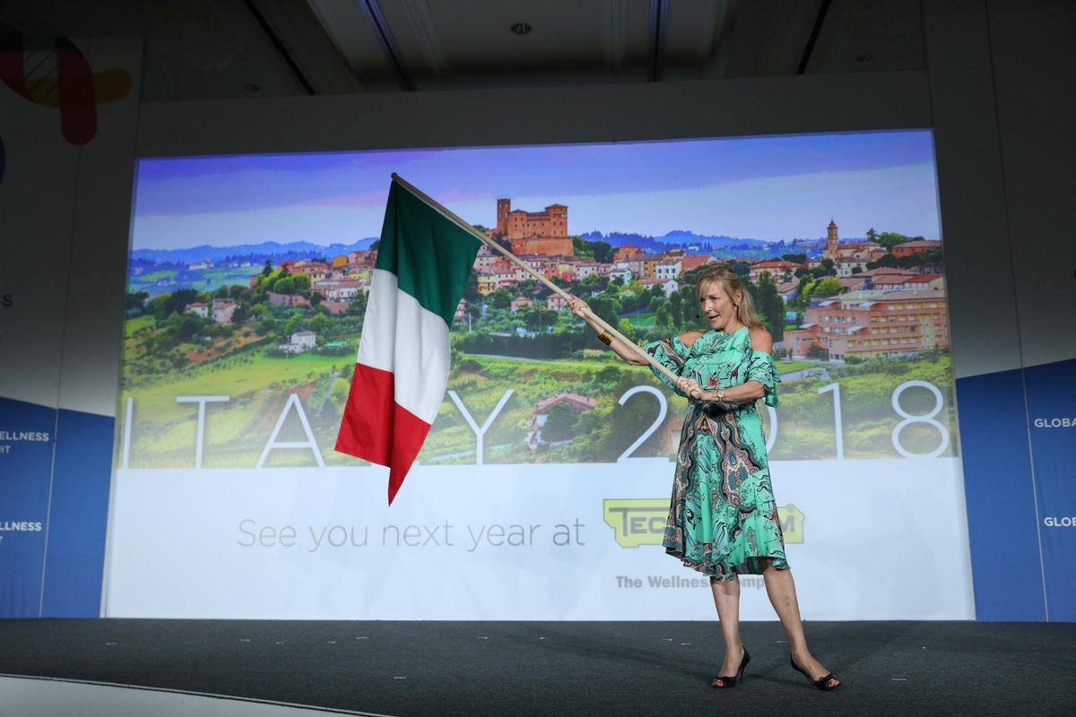 Susie Ellis, Global Wellness Summit chair and CEO, waves the Italian flag as she makes the announcement about the location of the 2018 Summit