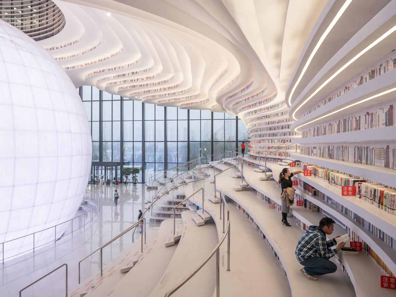 Floor-to-ceiling bookcases cascade organically around the auditorium, forming the building's main spatial device / Ossip van Duivenbode