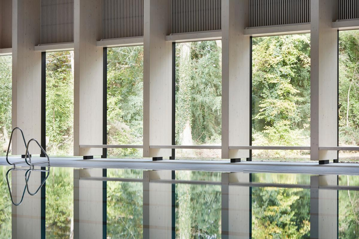 Swimmers using the 25m, six lane competition pool can view the surrounding woodland through a series of windows integrated into the building's timber frame / Jack Hobhouse