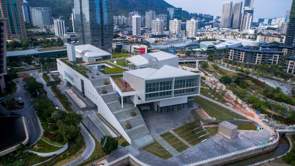 The Sea World Culture and Arts Center (SWCAC), located in Shenzhen Bay, is formed of three white cantilevered volumes atop a deconstructed plinth / Design Society