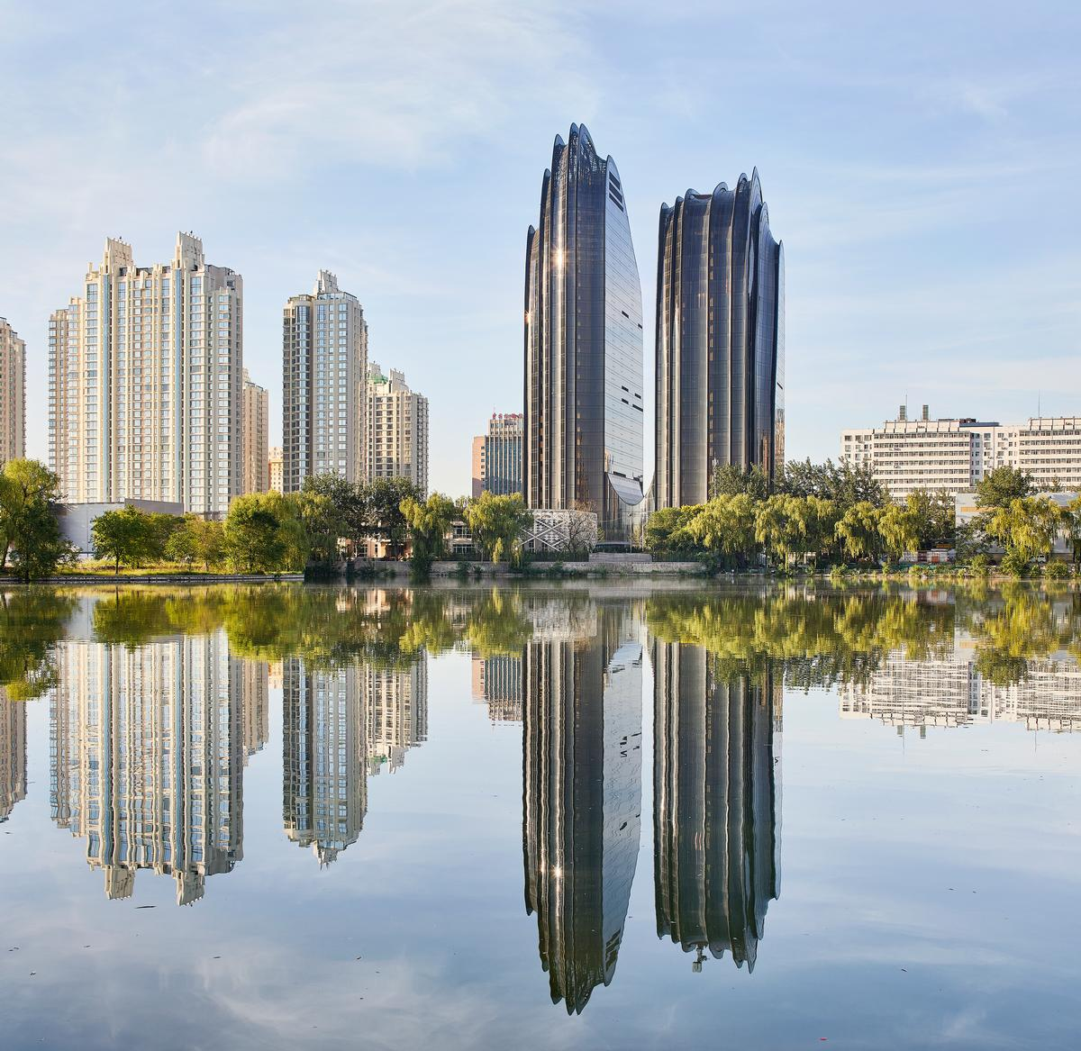 Two asymmetrical twin tower office buildings on the north side of the site sit at the base of the park's lake and evoke a pair of mountain peaks growing out the water / Hufton + Crow