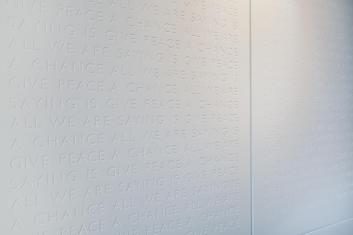 The lyrics to 'Give Peace a Chance' are inscribed repeatedly on the walls in the style of a war memorial. / Fairmont Le Reine Elizabeth