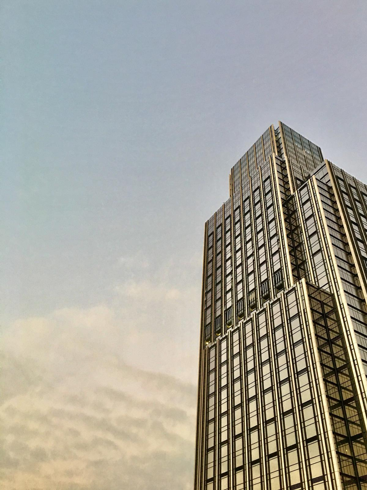 The tower incorporates Portuguese limestone accented with bronze trims / New World Development