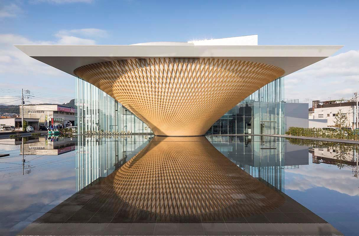 The shape of a volcano is formed in the large reflecting pool situated at the front of the complex / Shigeru Ban Architects