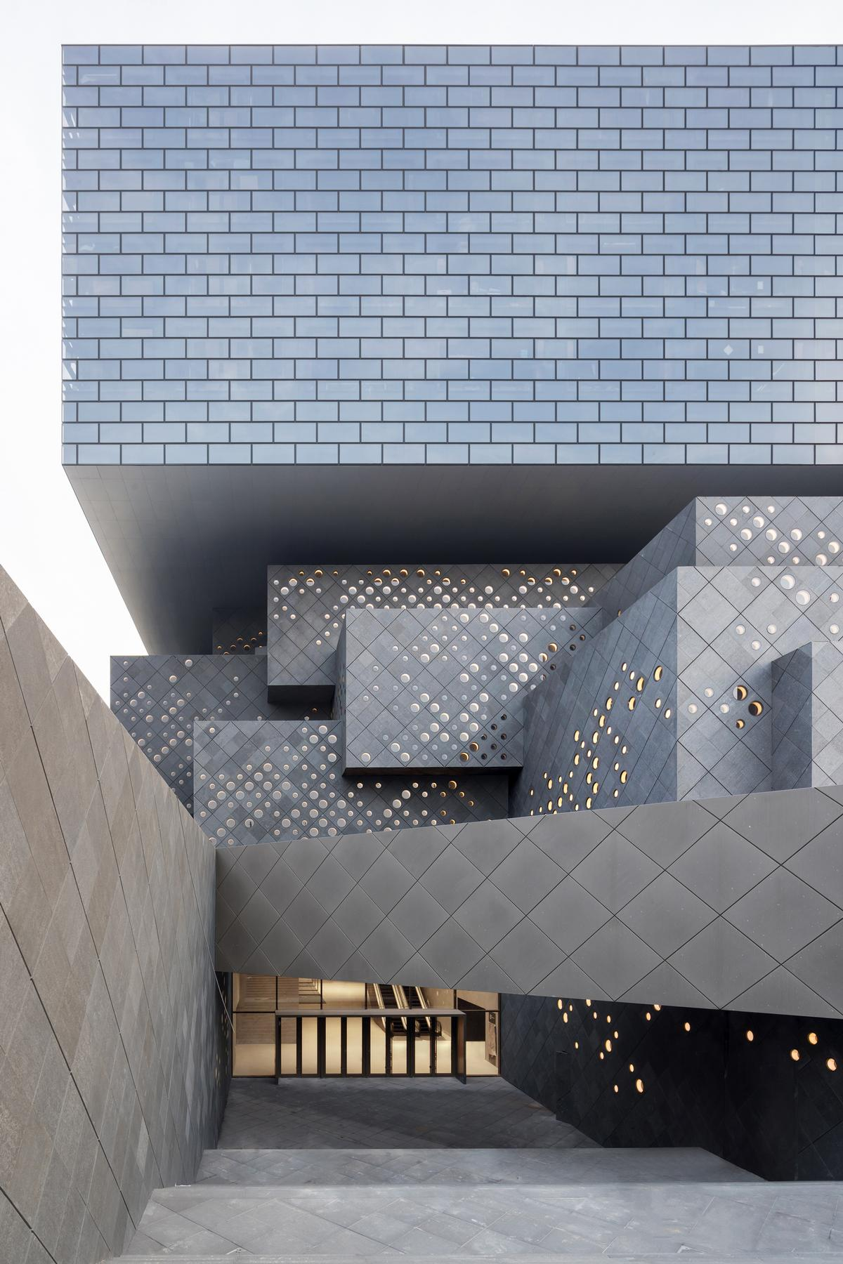 The lower portion is a series of nested stone volumes that echo the scale and materiality of the adjacent hutong courtyard houses, while a floating glass ring above acknowledges modernity / Iwan Baan