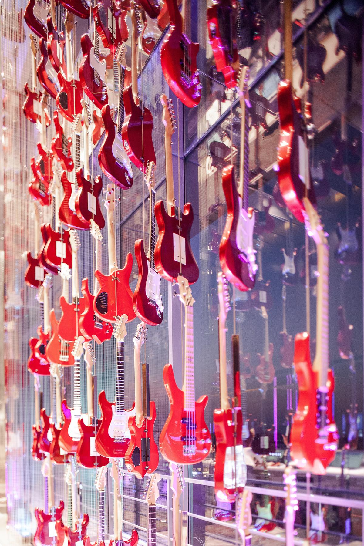 A wall of 160 red guitars stands behind the reception desk / Nirut Benjabanpot