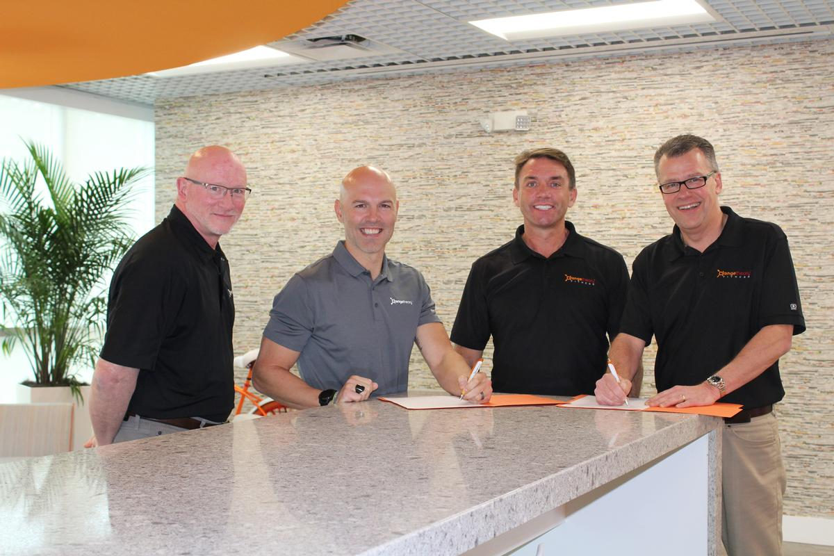 Dave Carney, president Orangetheory (left), with Orangetheory CEO Dave Long (second left) signing the master franchisee deal with Mike Dixon, chair of Wellcomm Health & Fitness (second right) and Alistair Firth, CEO of Wellcomm Health & Fitness (right)