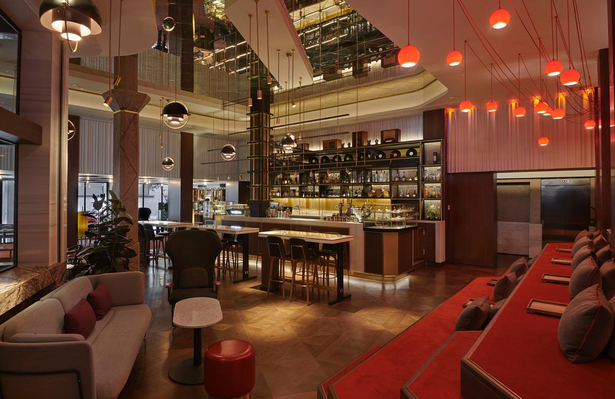 The hotel's bar is formed of three individual 'radio pods' of brass and walnut with a giant antenna stretching across the ceiling / Blue Sky Hospitality