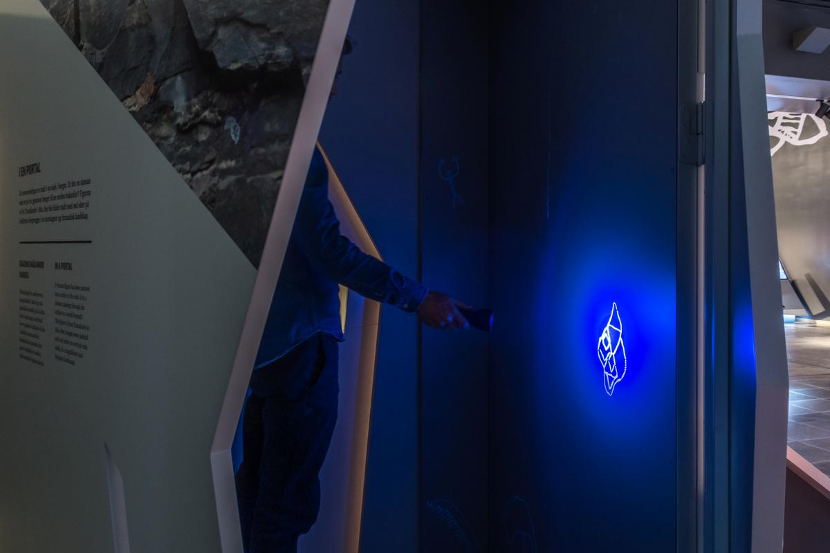 Visitors can generate luminescent rock carvings in the dark by torchlight / Kvorning Design & Communication