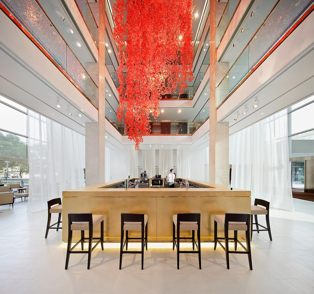 The red ceiling sculpture by Jacopo Foggini creates a dramatic contrast to the all-white interior / Photos of the Hilton Barcelona: Peguenaute