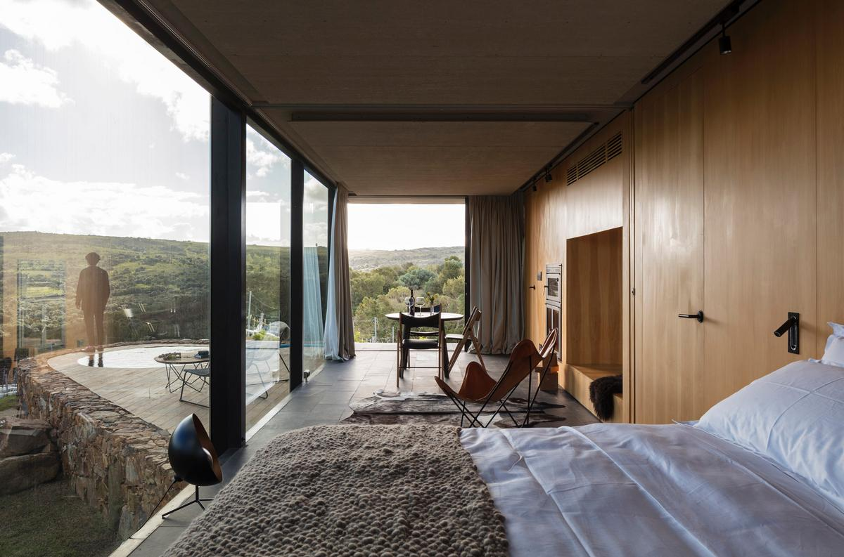 The main space contains the bedroom, living and dining room, which opens fully onto the landscape. / Leonardo Finotti