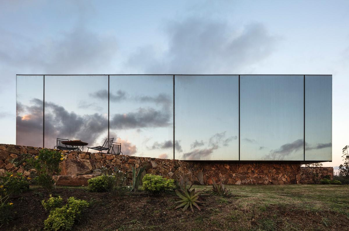 The facade is composed by a sheet of one-way mirror, covering the cabin with an almost magical effect, creating a tense limit between both the camouflage and the rhythm of nature / Leonardo Finotti