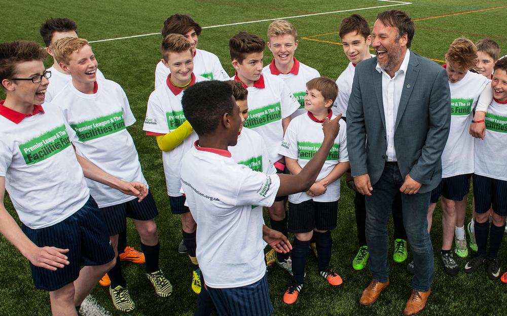 Former Arsenal player Paul Merson shares a joke as he cuts the ribbon on another facility