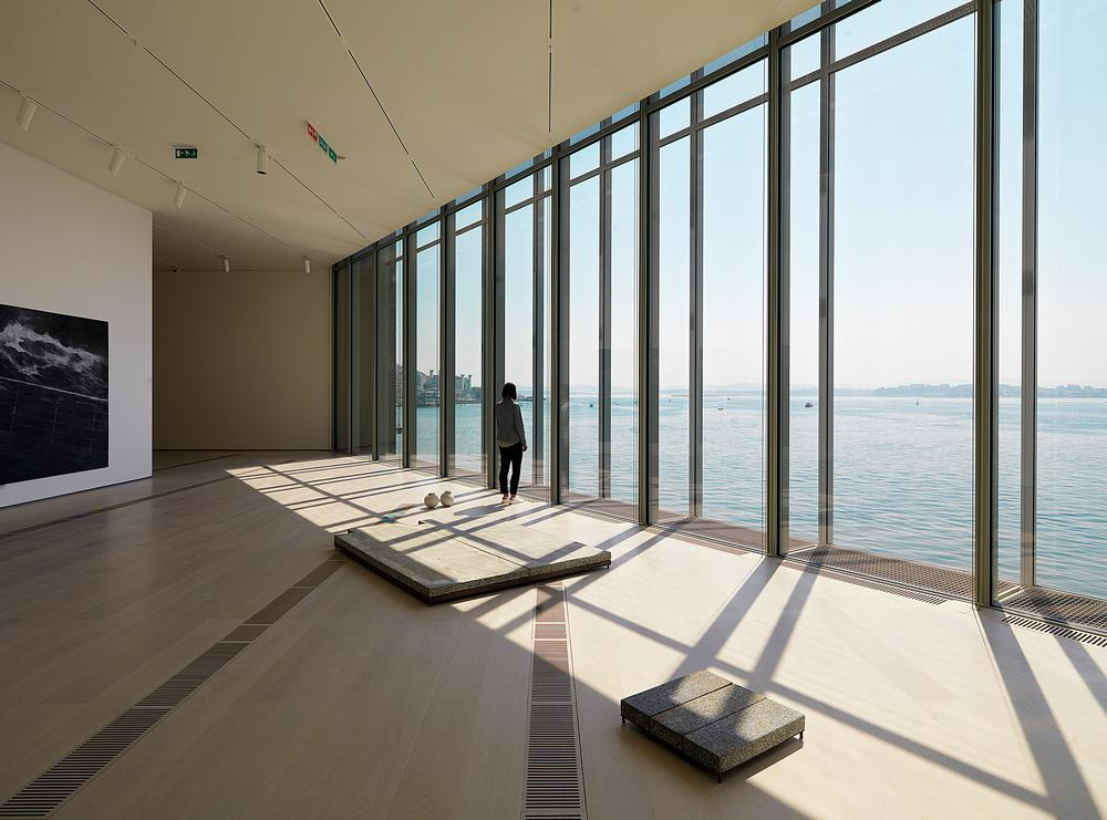 The building extends out and over the waterfront, creating impressive views across the sea