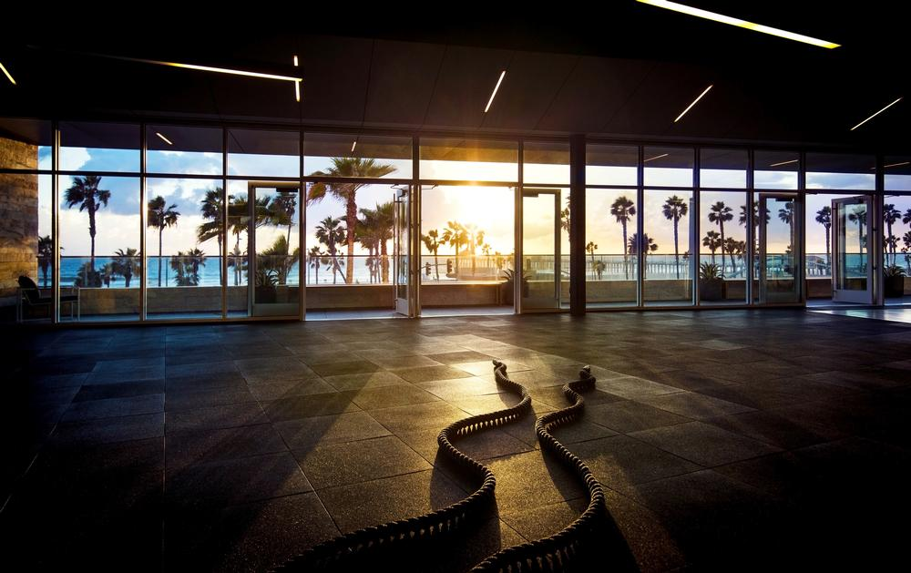 Floor to ceiling windows frame the view of the beach at Equinox Huntington in California